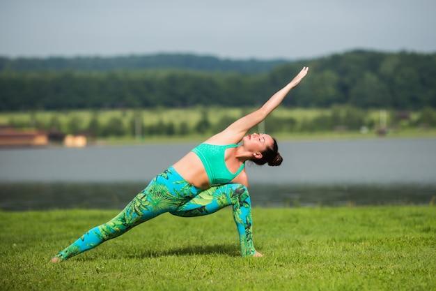 Fitness-frau, die yoga-übung macht und sich mit sportbekleidung im grünen park im sommer entspannt