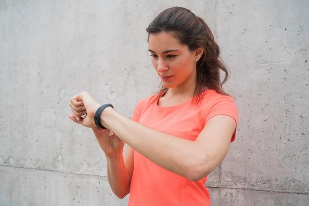 Fitness-frau, die zeit auf smartwatch prüft.