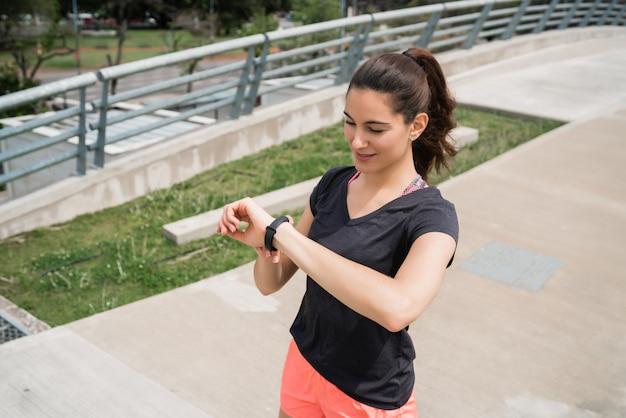 Fitness-frau, die zeit auf smartwatch prüft