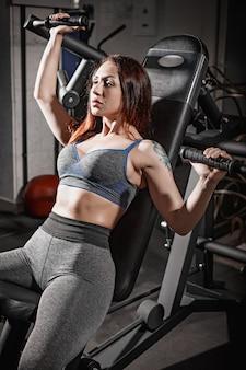 Fitness frau gewichtheben training im fitnessstudio