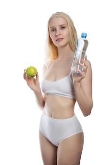 Fitness frau glücklich lächelnd halten apfel und wasserflasche. gesundes lebensstilfoto des kaukasischen fitnessmodells lokalisiert auf weißem hintergrund.
