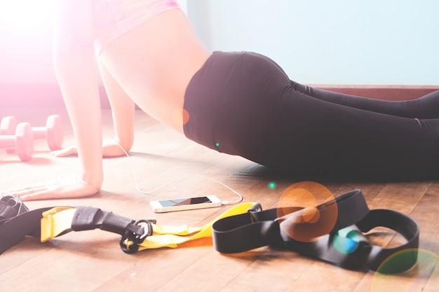 Fitness-frau in schwarzen hosen und rosa sport-bh stretching nach dem training mit kopie raum