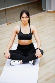 Fitness frau. junge attraktive frau, die übungen in der eignungsturnhalle tut