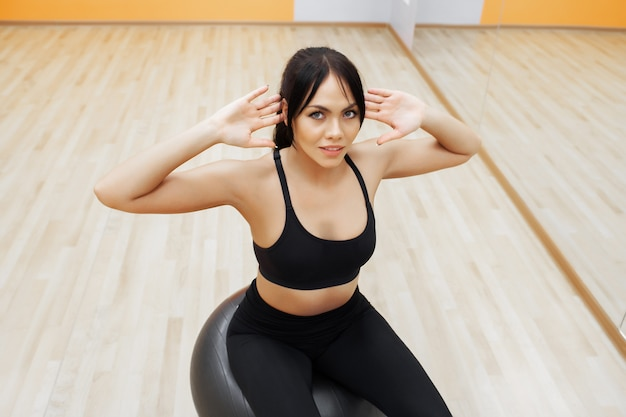 Fitness frau. junge attraktive frau, die übungen unter verwendung der kugel tut