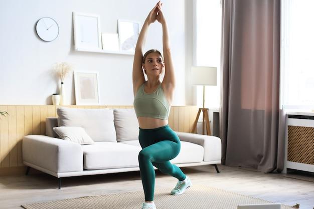 Fitness-frau macht sportübungen und sieht sich online-tutorials auf dem laptop an, trainiert im wohnzimmer. bleiben sie zu hause aktivitäten.