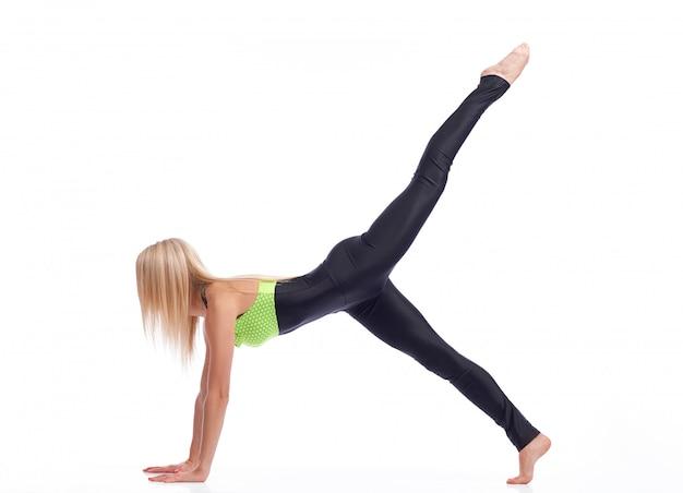 Fitness-frau mit starker körperdehnung, die ihr bein in der luft hält, die plankenübung macht