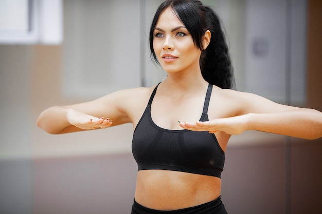 Fitness frau. sportmädchen in der turnhalle, die übungen tut