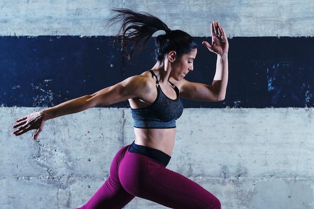 Fitness frau übung springen in der turnhalle