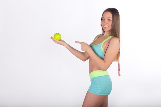 Fitness-frau zeigt mit dem finger auf apfel, maßband auf der schulter, weißer hintergrund, seitenansicht. vitaminpflege, gesunde ernährung. gesunder lebensstil