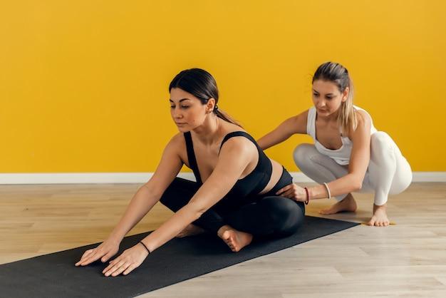 Fitness-frauentraining mit ihrem persönlichen trainer im fitnessstudio. junges paar macht dehnübungen, kopienraum.