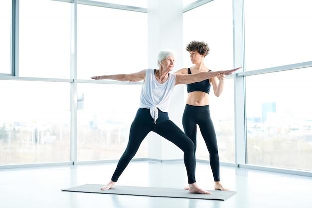Fitness für senioren. frauen auf matte machen yoga neben einem großen fenster