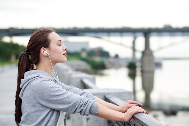 Fitness gesunde asiatische frau läufer entspannend nach dem laufen im freien genießen blick auf die uferpromenade