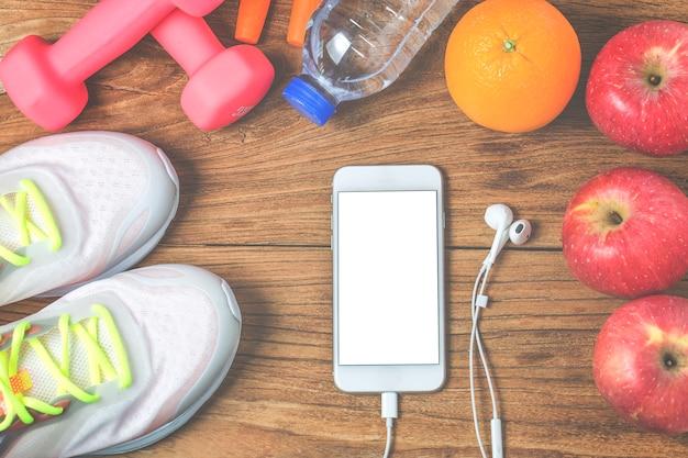 Fitness, gesunde und aktive lebensstile konzept, eine flasche wasser, hanteln, sportschuhe, smartphone mit kopfhörer und äpfel auf holz hintergrund. kopieren sie platz für text. draufsicht
