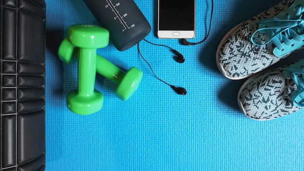 Fitness-hintergrund. ausrüstung für fitnessstudio und zuhause. blauer hintergrund draufsicht kopie raum