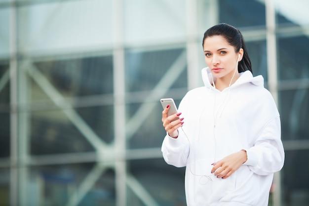 Fitness. hörende musik der frau am telefon beim draußen trainieren - sport und gesundes lebensstilkonzept