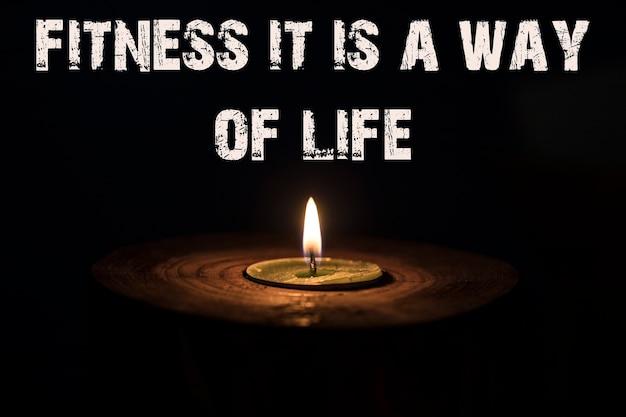Fitness ist ein lebensgefühl - weiße kerze mit dunklem hintergrund - in einem holzkerzenständer.