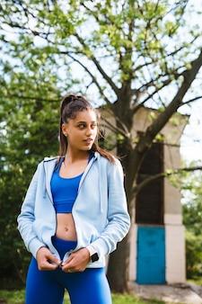 Fitness junge frau geht in den park und posiert