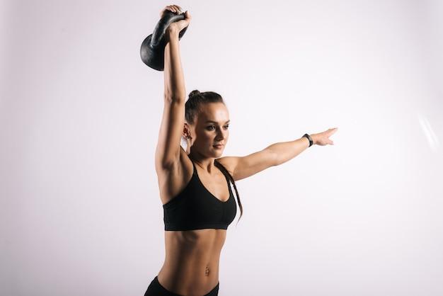 Fitness junge frau mit perfektem muskulösen körper anhebender kettlebell overhead