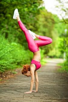 Fitness. junge schöne frau, die in den park ausdehnt