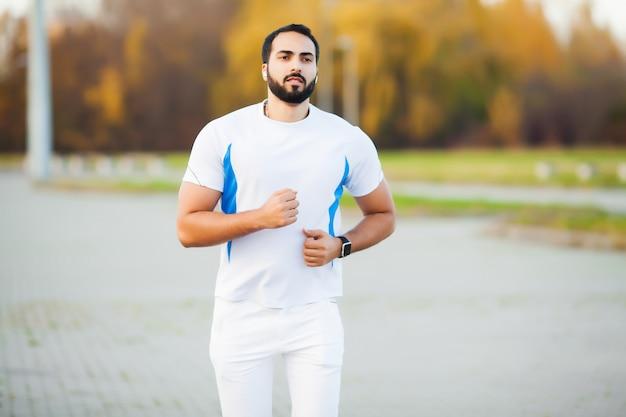 Fitness. junger mann, der in der städtischen umgebung läuft