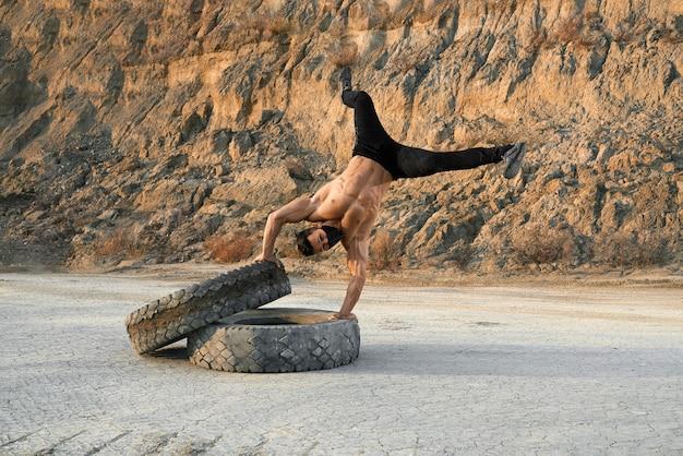 Fitness junger mann mit nacktem oberkörper, der auf händen auf zwei großen reifen steht, während draußen trainiert.