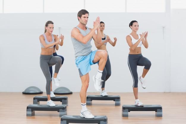 Fitness-klasse, die stepp-aerobic-übung durchführt