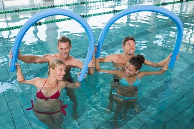 Fitness-klasse macht aqua-aerobic mit schaumrollen