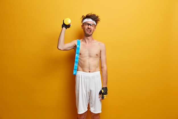 Fitness, kraft und sportliches lifestyle-konzept. unzufriedener erwachsener mann im stirnband weint, als er eine schwere hantel hebt, die des schwierigen trainings müde ist, mit maßband posiert und seine körperform kontrolliert