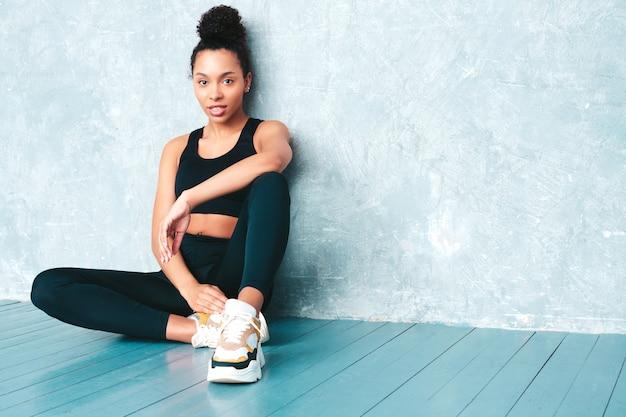 Fitness lächelnde frau in sportkleidung mit afro-locken-frisur