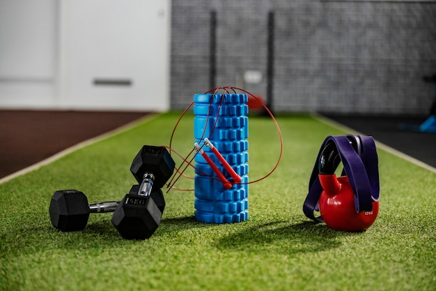 Fitness lebensstil und ausrüstung. sportgeräte auf grünem kunstrasen im fitnessstudio - walze, hantel, gummiband und wasserkocher. die wände des fitnessraums sind verschwommen, konzentrieren sie sich auf den vordergrund