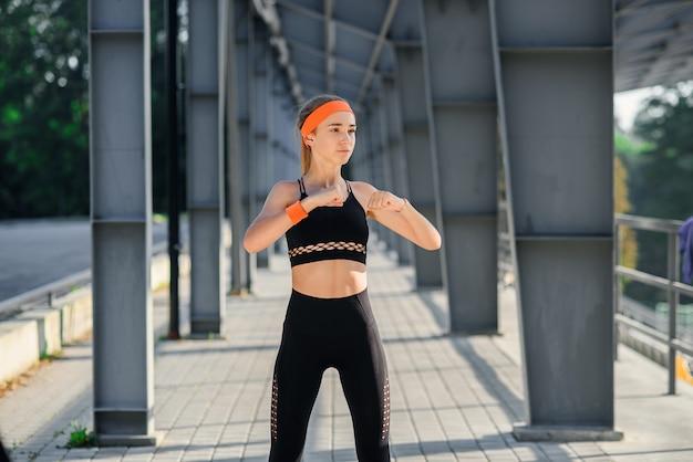 Fitness-mädchen bei sportbekleidung macht übungen im sportstadion.