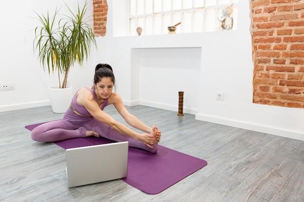 Fitness-mädchen, das yoga im wohnzimmer tut. sie streckt ihren körper, während sie auf ihren laptop schaut. sportkonzept und online-training von zu hause aus. platz für text.