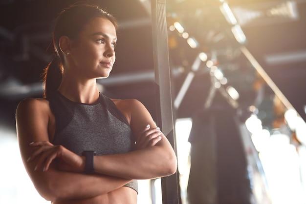 Fitness mädchen junge attraktive fit frau trägt sportkleidung, die arme verschränkt hält und wegschaut