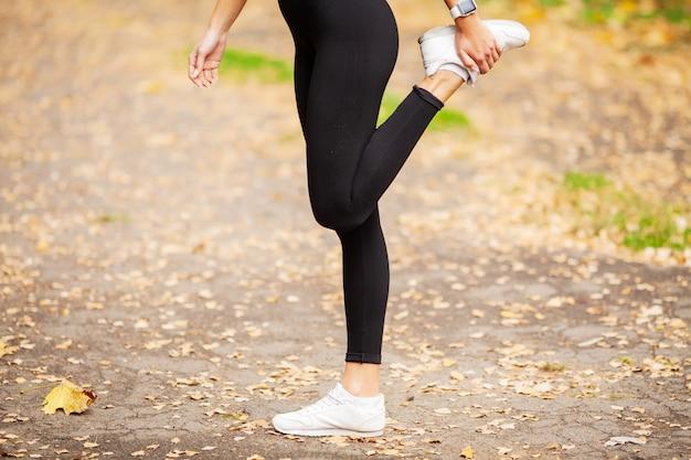 Fitness mädchen. junger eignungsfrauenläufer, der beine vor lauf ausdehnt