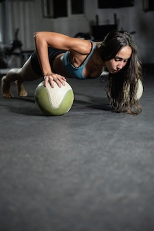 Fitness-mädchen macht liegestütze auf den bällen