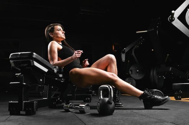 Fitness-mädchen mit baggern, die auf einer bank im fitnessstudio aufwerfen