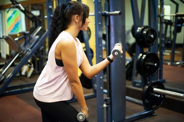 Fitness mädchen. sexy athletisches mädchen, das in der turnhalle ausarbeitet. eignungsfrau, die übung tut
