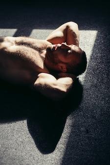Fitness-männchen, das im fitnessstudio trainiert. muskulöser junger mann, der magenübungen macht.