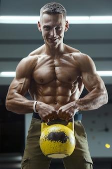 Fitness-mann beim training im fitnessstudio, das muskeln mit kettlebell aufpumpt.