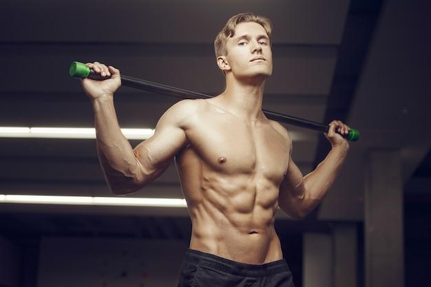 Fitness-mann beim training im fitnessstudio mit bodybar-streckmuskeln. workout fitness und bodybuilding konzept. kaukasischer bodybuilder, der bauchmuskelübungen im fitnessstudio macht