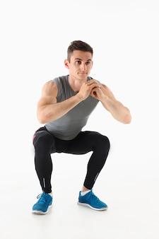 Fitness mann crouchs vom boden demonstriert