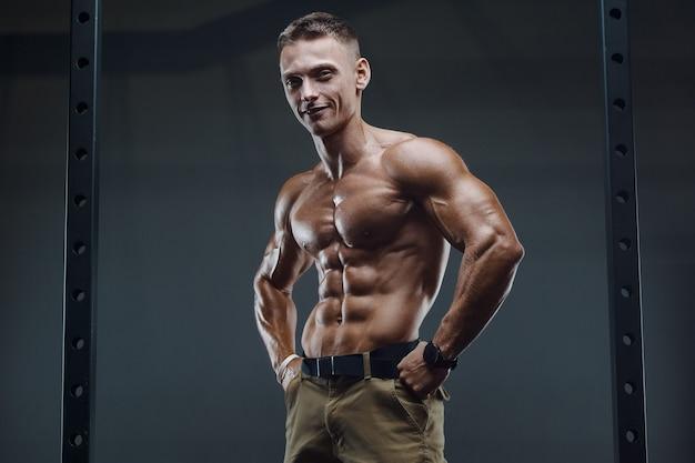Fitness-mann, der bauchmuskeln im fitnessstudio aufpumpt