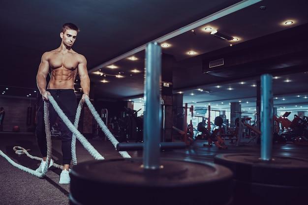 Fitness-mann, der mit kampfseilen im fitnessstudio arbeitet.