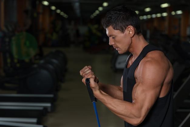 Fitness-mann, der mit stretching-band in der turnhalle trainiert. muskulöser sportmann, der mit gummiband trainiert.