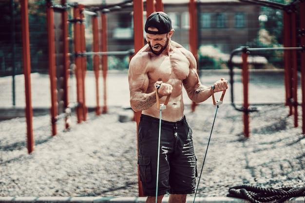 Fitness-mann, der mit stretchingband im fitnessstudio im freien trainiert