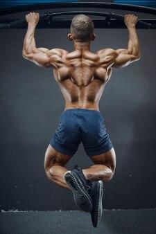 Fitness-mann, der muskel aufpumpt, der klimmzugübungen macht