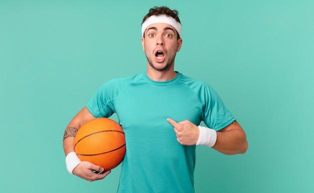 Fitness-mann, der schockiert und überrascht mit weit geöffnetem mund aussieht und auf sich selbst zeigt