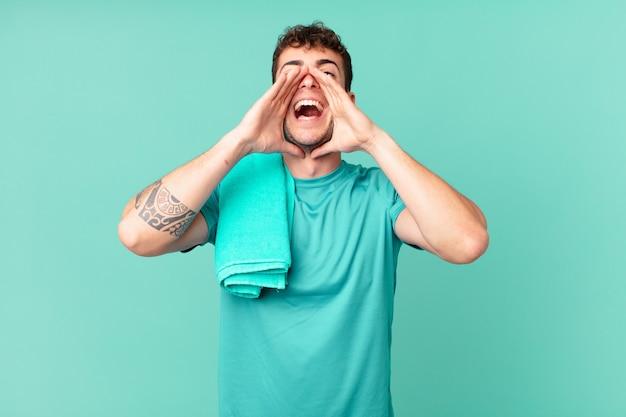 Fitness-mann, der sich glücklich, aufgeregt und positiv fühlt, mit den händen neben dem mund einen großen schrei ausstößt und ruft