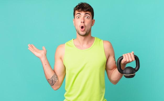 Fitness-mann, der überrascht und schockiert aussieht, mit heruntergefallenem kiefer, der einen gegenstand mit offener hand an der seite hält