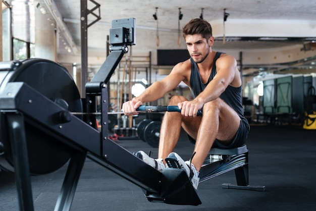 Fitness-mann, der übung im fitnessstudio macht. wegschauen